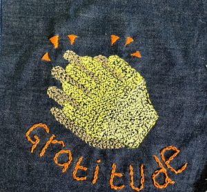 'Gratitude' stitched onto a piece of fabric