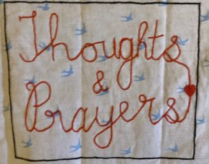 'Thoughts and prayers' stitched onto a piece of fabric