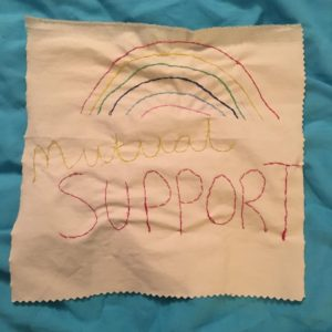 'Mutual Support' stitched onto a piece of fabric