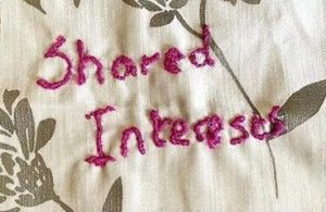 'Shared interests' stitched onto a piece of fabric